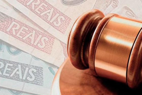 Foto da parte superior de um martelo de juiz sobre notas de dinheiro