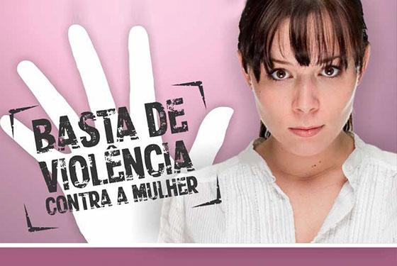Imagem com uma mulher olhando para frente e uma mão com a seguinte mensagem escrita: Basta de Violência contra a mulher