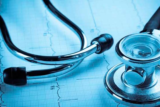 imagem de um estetoscópio em cima de uma folha com leitura de batimentos cardíacos. A imagem é toda em tons azuis