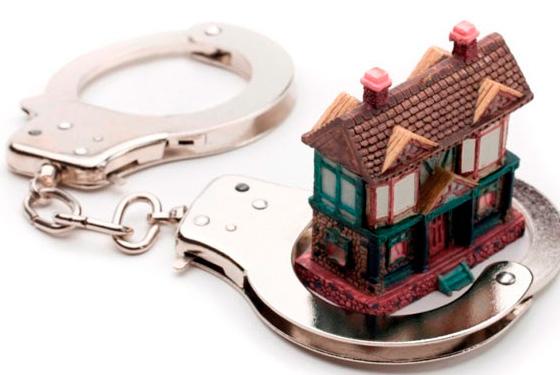 Algemas sobre uma superfície branca com uma casa em miniatura dentro da argola direita.
