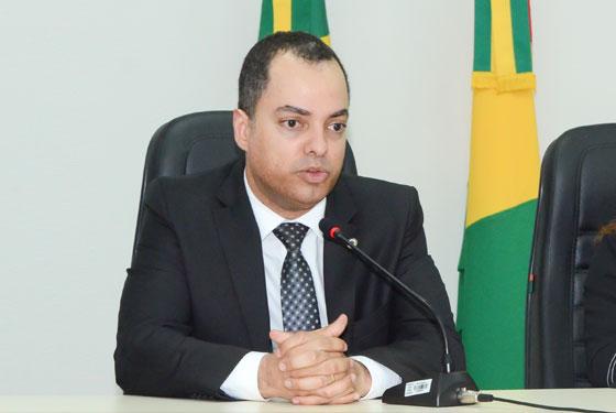 Fotografia do juiz Hugo sentado em uma mesa, com as mãos  cruzadas sobre a mesa e bandeiras atrás