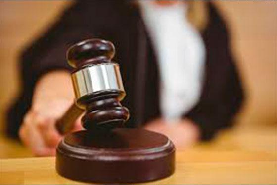 Foto de um martelo de madeira, usado por juízes, sendo segurando por uma mulher em vestes de juiz