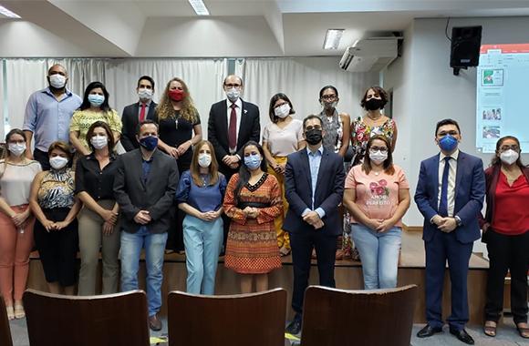 Imagem com participantes da reunião alinhados em duas fileiras. Todos usam máscaras de proteção no roto.