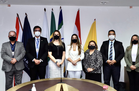 foto de sete pessoas de pé com bandeiras ao fundo