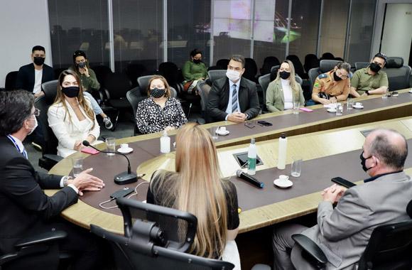 Foto de uma mesa de reuniões em U, com participantes sentados em volta e usando máscara