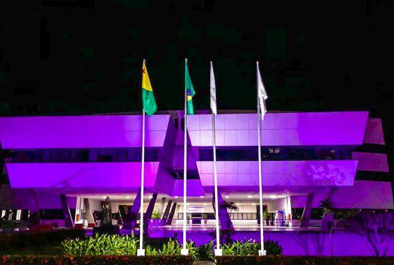 Fotografia da sede do Tribunal de Justiça do Acre, mostrando a que o prédio está iluminando na cor lilás