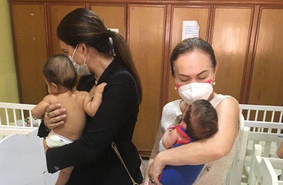 Fotografia da juíza de Direito Andréa Brito à esquerda e à direita a desembargadora Regina Ferrari segurando bebês no colo. Não aparece o rosto dos bebês. Ao fundo tem berços esparramados e um armário.