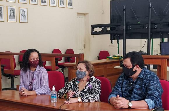 foto de uma mesa com três pessoas, da direita para esquerda prefeita da cidade de Tarauacá, desembargadora Eva Evangelista e presidente da câmara de vereadores da cidade.