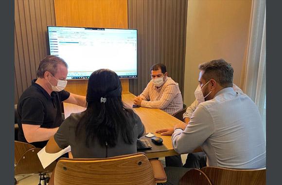 Fotografia de cinco pessoas sentadas em volta de uma mesa de reunião, com uma televisão ao fundo. Todos usam máscaras de proteção facial.