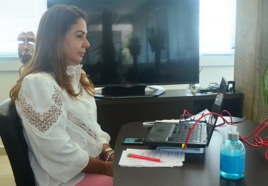 Fotografia da presidente, desembargadora Waldirene Cordeiro, sentada olhando pra a tela do notebook