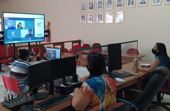 Fotografia da sala de audiência do Fórum em Tarauacá. Aparecem três mulheres sentadas na mesa em formato de T, separadas por placas de acrílico. Duas estão olhando para um monitor de TV no fundo esquerdo da imagem e outra olha para a tela do computador na frente dela.