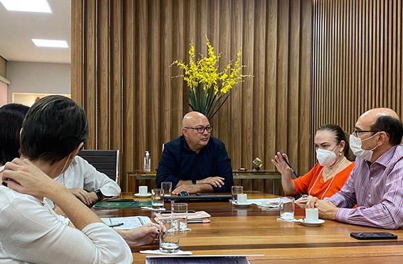 Fotografia de seis pessoas sentada em uma mesa de reunião conversando.