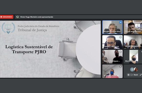 """Imagem da vídeochamada com os quadradinhos dos participantes em coluna no lado direito e no lado esquerdo um slide escrito """"Logística Sustentável de Transporte TJRO"""""""