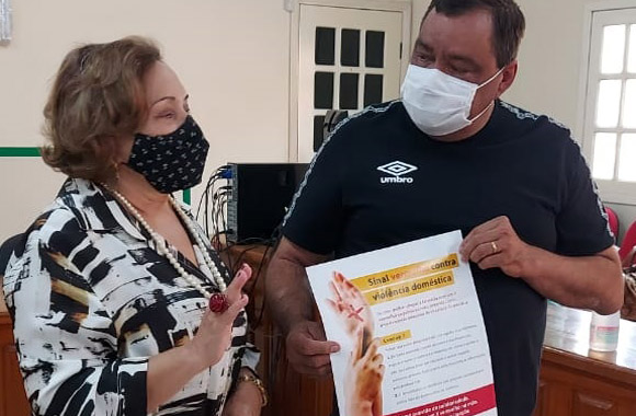 Desembargadora Eva Evangelista conversando com prefeito da cidade, que está segurando um cartaz da Campanha Sinal Vermelho contra a Violência Doméstica