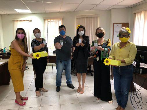 Equipe da Gerência de Qualidade de Vida ao lado dos servidores do setor de comunicação do TJAC posando para foto. Todos seguram saquinhos com folhas de chá