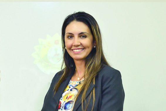 Foto da juíza Andréa Brito olhando na direção da câmera e sorrindo