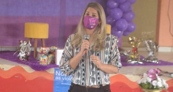 Fotografia da juíza de Direito Louise Kristina, falando ao microfone. Atrás dela tem um palco decorado na cor lilás com bexigas, tapete e presente esparramado por cima do palco.