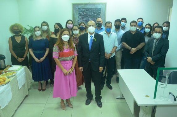 Foto da presidente do TJAC, desembargadora Waldirene Cordeiro ao lado do vice-presidente, desembargador Roberto Barros, de pé à frente da equipe de servidores da Diretoria de Pessoas do Tribunal de Justiça