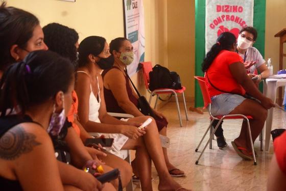 fila de mulheres esperando ser atendida e ao fundo a psicologa do TJAC atendendo uma pessoa