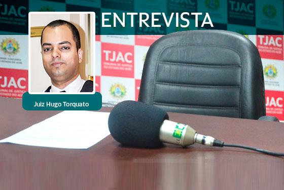 Foto do microfone e uma folha de papel sobre uma mesa, atrás uma cadeira e um banner com a logomarca do TJAC e por cima da imagem um quadradinho com a foto do juiz Hugo Torquato e ao lado a palavra entrevista