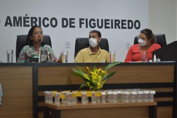 Foto da mesa de honra com a assistente social falando e duas pessoas olhando para ela